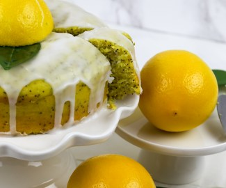 a cake stand with vegan lemon drizzle cake and lemons