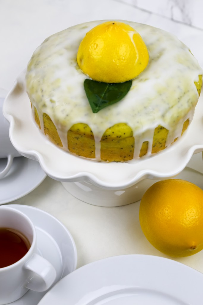 a cake stand with vegan lemon drizzle cake and tea