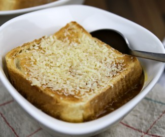 a bowl with vegan french onion soup on cloth